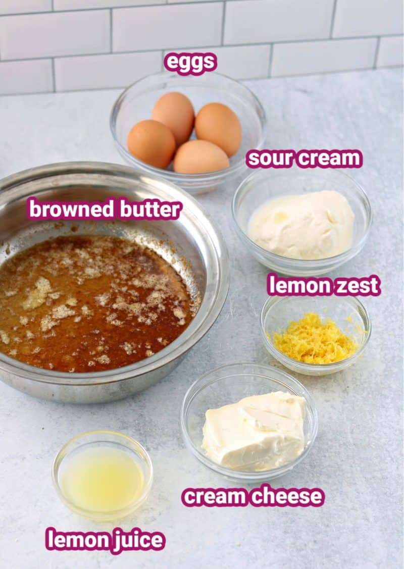 keto lemon cake wet cake ingredients with text to label the eggs, sour cream, cream cheese, browned butter, lemon juice and lemon zest