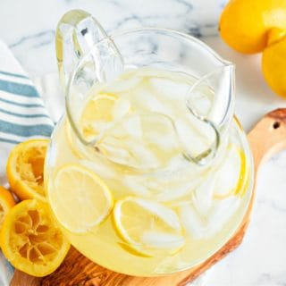 a pitcher of keto lemonade on a wooden board with sliced lemons