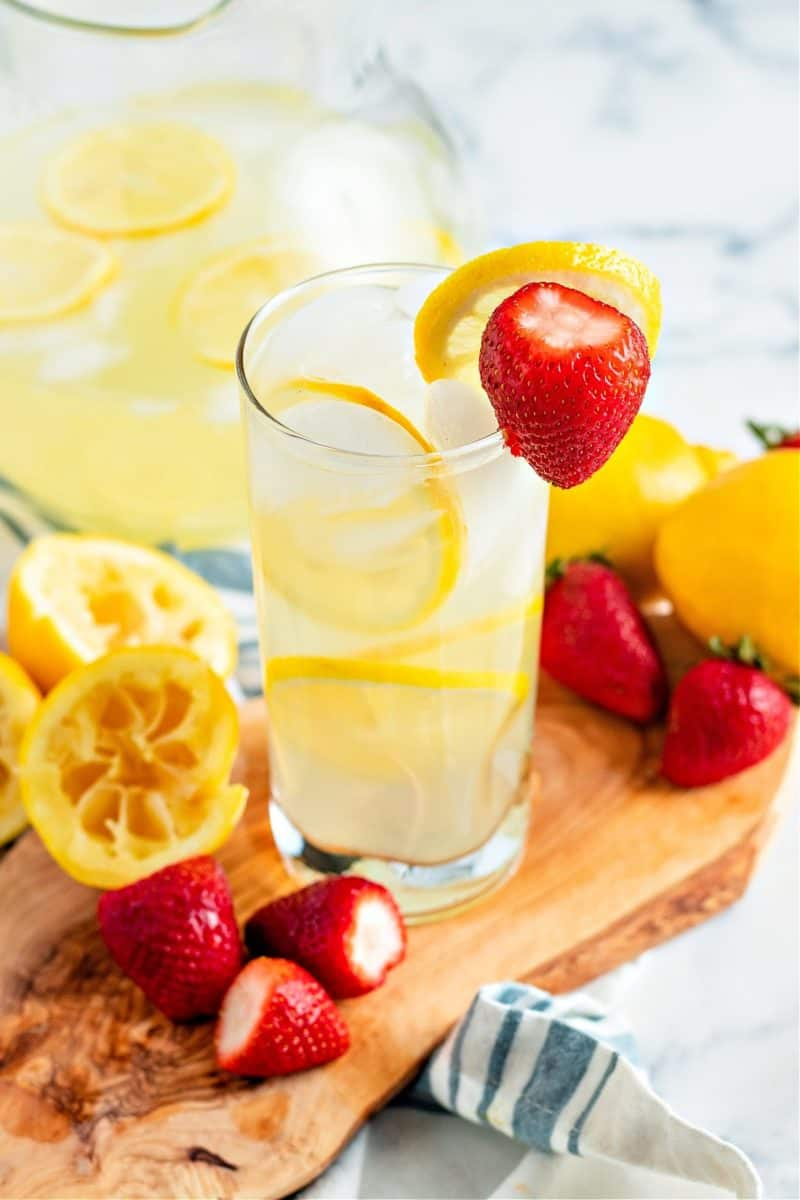 a close-up of glass of keto lemonade on a wooden board with lemon slices and strawberries