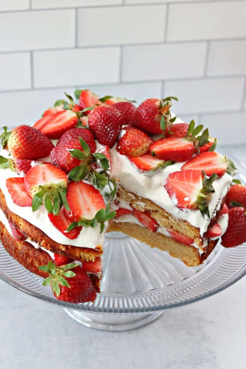 double layer low carb strawberry shortcake on a cake stand with a slice cut out