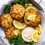 a close-up of six air fryer crab cakes in a metal bowl with lemon, dill, parsley, and homemade tartar sauce