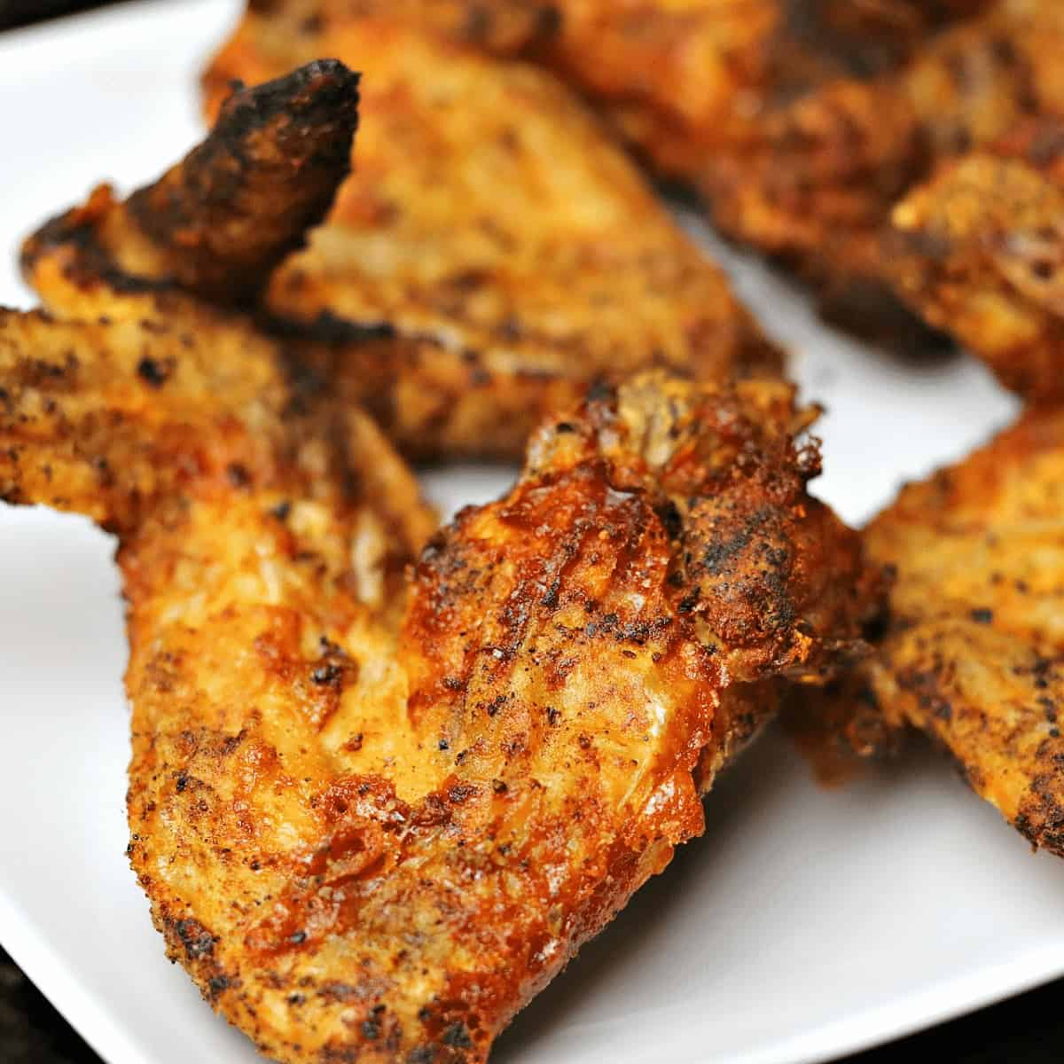 a close-up of an air fryer fried chicken wing on a white plate