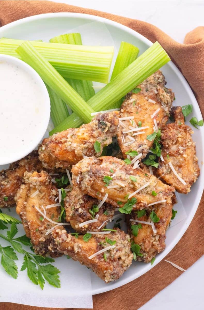 a plate of air fryer garlic parmesan wings on a plate with ranch dipping sauce and celery