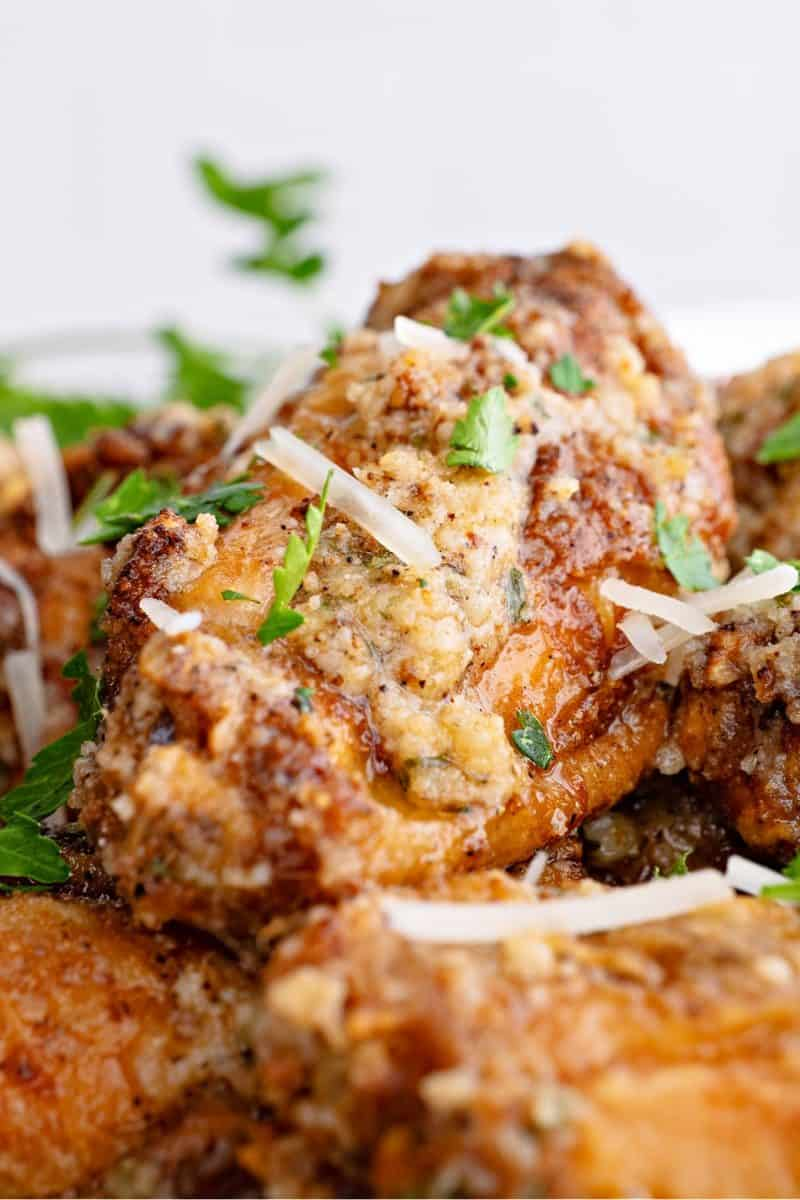 a close-up of a garlic parmesan wing on a plate with parsley and parmesan shreds on top