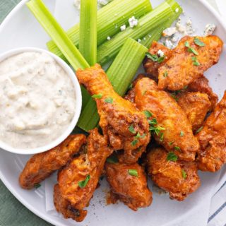 keto buffalo wings on a white plate with homemade blue cheese dressing and celery