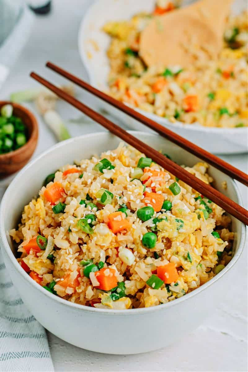 keto cauliflower fried rice in a bowl and a pan