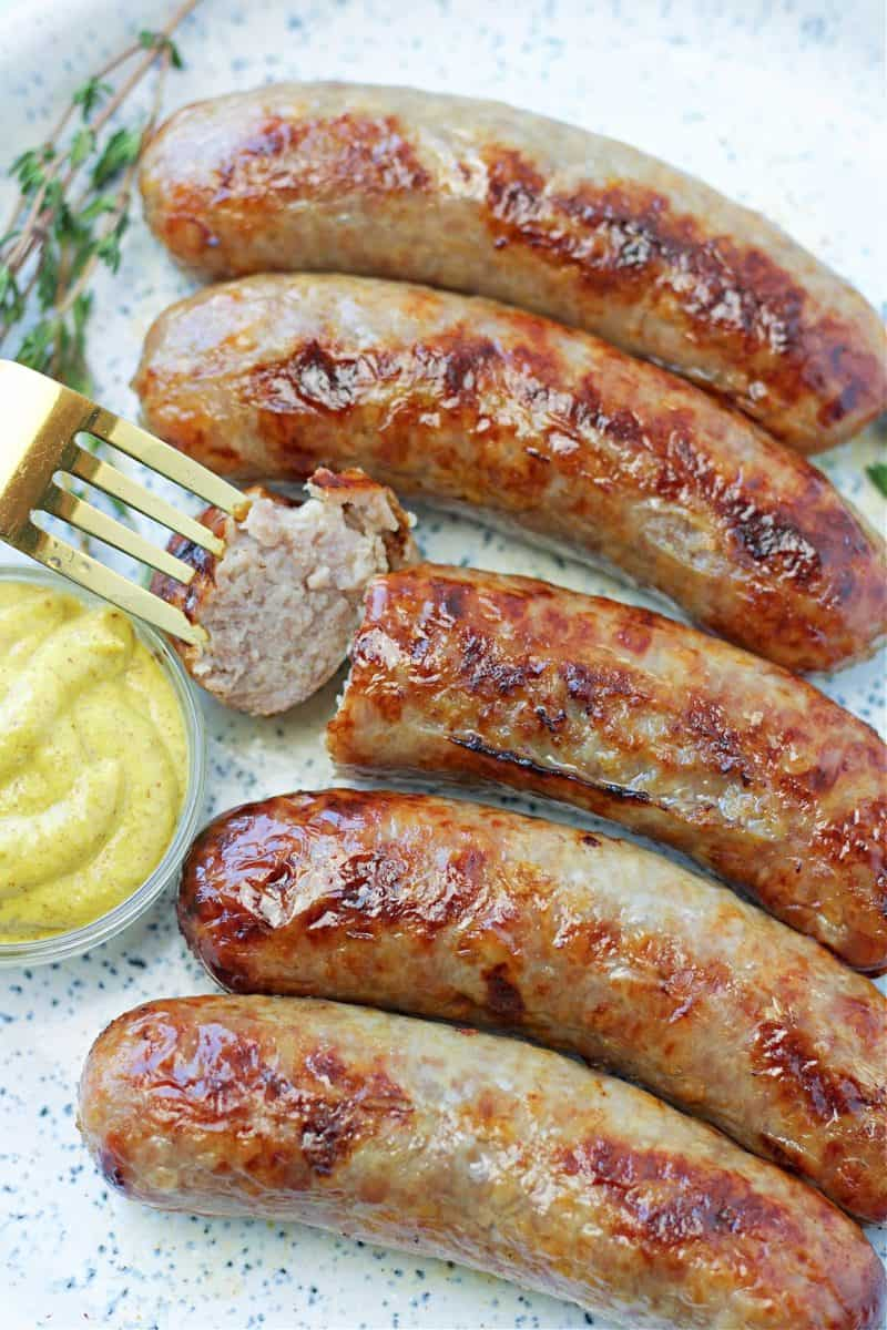 a plate of air fryer brats on a plate with dijon mustard