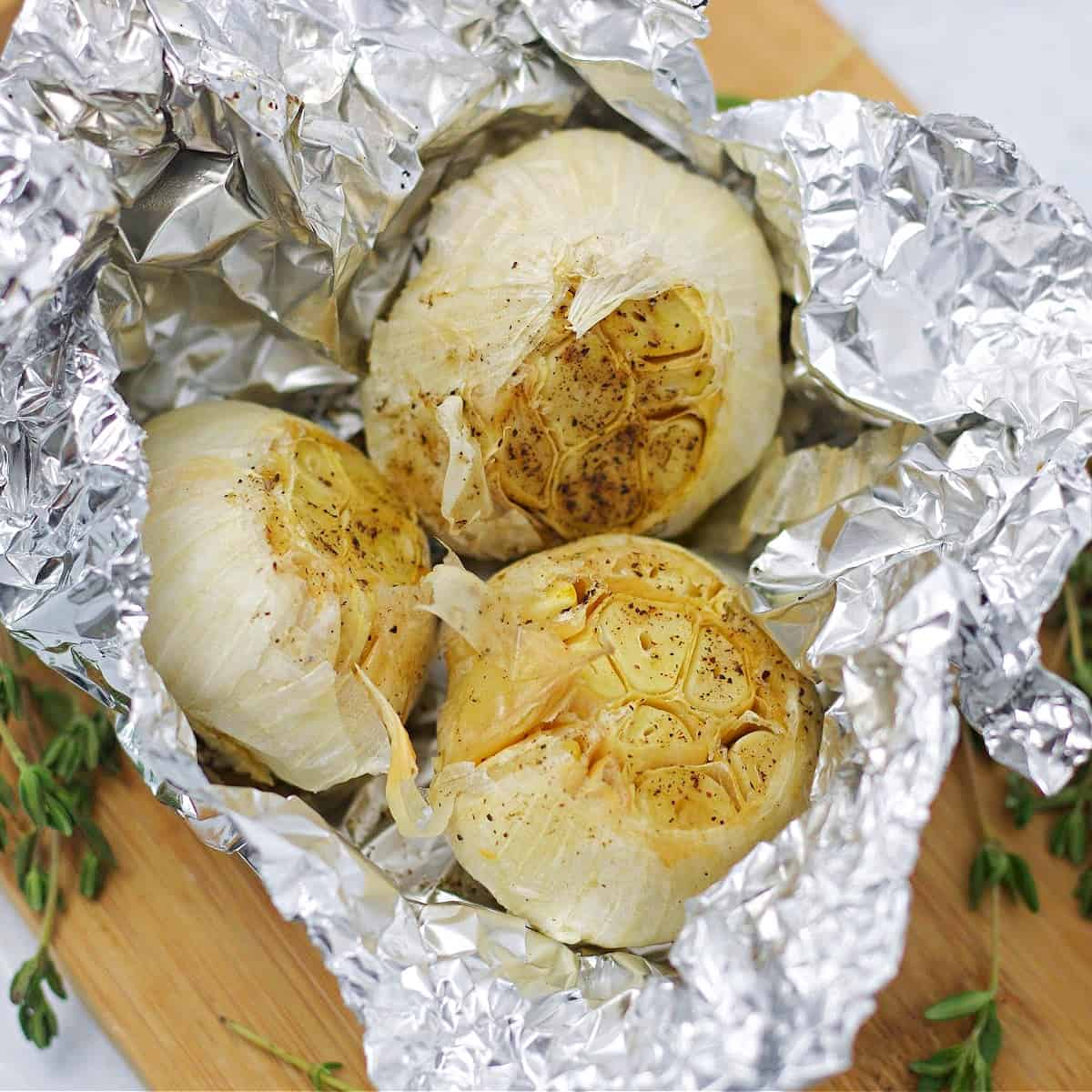 three garlic bulbs roasted in foil with thyme