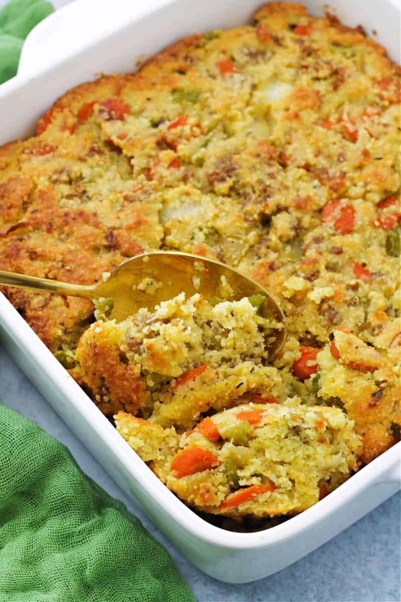 keto cornbread stuffing in a white baking dish with a spoon